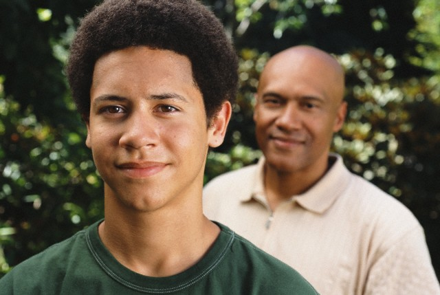 Father and teenage son standing outdoors --- Image by © Ocean/Corbis